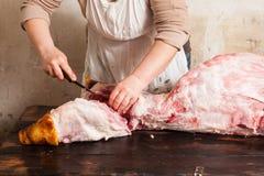 Slaktare som snider rått griskött i lokal marknad Fotografering för Bildbyråer