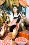 Slaktaren med späcker och kött i räknare av lagret Arkivbild