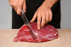 Slaktaren som klipper nytt rått kött på räknare shoppar in arkivfoto