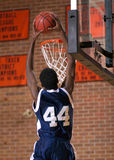 Slam Dunk. Male basketball player leaping high to slam dunk a basketball during a game in an old brick-lined gym Royalty Free Stock Photo