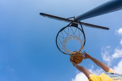 Slam dunk in basketball. Outdoors with blue sky royalty free stock photography