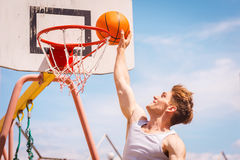 Slam Dunk. Side view of young basketball player making slam dunk royalty free stock images