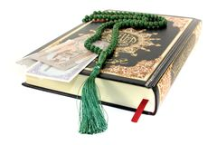 Slammed Quran with Pakistani currency. Before light background Royalty Free Stock Images