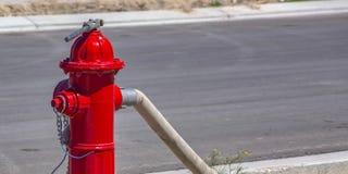 Slang en moersleutel aan een rode brandkraan wordt beveiligd die stock foto