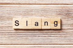 Slang word written on wood block. slang text on table, concept.  Royalty Free Stock Photos