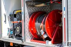 Slangen en ander brandbestrijdingsmateriaal aan boord van een brandvrachtwagen stock foto