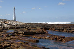 Slangkop lighthouse. Rocky coastline of Kommetjie with Slangkop lighthouse in background, Cape Peninsula, South Africa Stock Images