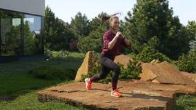 Slank atletisch mooi Kaukasisch meisje die geschiktheidsoefeningen op de aard doen De mooie vrouw maakt het springen met op st ui stock videobeelden
