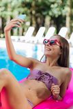 Slank beroemd model die selfie ontspannend in de pool maken stock foto's