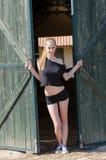 Slank blonde die zich voor van de boxdeur bevinden Stock Fotografie