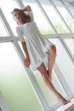 Slank blonde in mooie de zomerkleding op venstervensterbank Royalty-vrije Stock Afbeeldingen