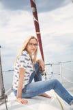 Slank blondin i jeans som sitter på näsa av den vita yachten Royaltyfria Bilder