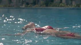 Slank dam i moderiktiga röda bikinibad i blå pöl för kristall lager videofilmer