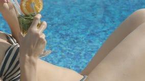 Slank dam som dricker den uppfriskande coctailen som tar solbadet nära rymlig pöl arkivfilmer