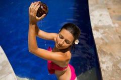slank donkerbruin jong wijfje die water geven met verse kokosmelk in pool met kristal blauw water Koninklijke tropische toevlucht royalty-vrije stock foto