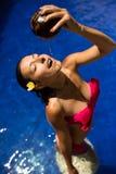 slank donkerbruin jong wijfje die water geven met verse kokosmelk in pool met kristal blauw water Koninklijke tropische toevlucht stock afbeeldingen