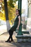 Slank donkerbruin meisje in groene kleding met bril door kolom a Stock Afbeeldingen
