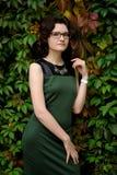 Slank donkerbruin meisje in groene kleding met bril in klimop Stock Foto's