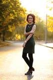 Slank donkerbruin meisje in groene kleding met bril in lege st Royalty-vrije Stock Afbeelding