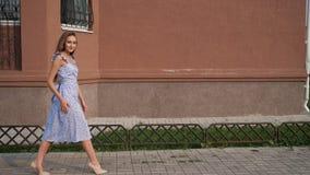 Slank Europees model in in blauwe kledingsgangen langs straat stock video