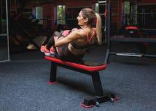 Slank gör kroppsbyggareflickan, övningarna för press i idrottshallen arkivbild