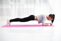 Slank geschikt meisje die de planking oefening van kernspieren doen royalty-vrije stock foto