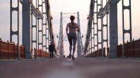 Slank hoger wijfje die over brug in stad lopen stock video