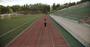 _ slank idrotts- flicka som joggar på stadion Attraktiv ung kvinna som utomhus övar lager videofilmer