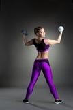 Slank idrotts- gymnast som övar med hantlar Royaltyfri Fotografi