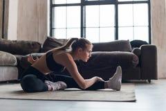 Slank idrottskvinna i sportswear som värmer muskler upp för genomkörare som gör sträcka övningssammanträde på golv hemma royaltyfria bilder