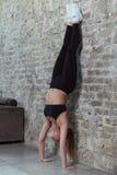 Slank idrottskvinna som gör praktiserande yoga för vägghandställning i en lägenhet med vindinre royaltyfri bild