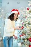 Slank jong meisje dichtbij de Kerstboom Stock Foto's