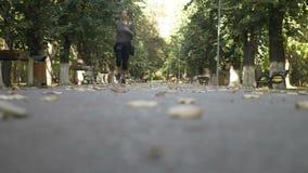 Slank jong meisje die aan muziek luisteren en in het park op een mooie zonnige de herfstdag lopen - stock video