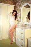 Slank kvinna i damunderkläder som poserar i sovrum Royaltyfri Foto
