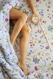 Slank kvinna som kopplar av i säng med latte Arkivbild