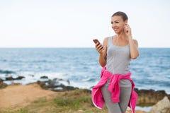 Slank kvinna som lyssnar till musik på stranden arkivfoto
