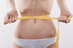 Slank kvinna som mäter midjan arkivfoton