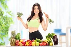 Slank kvinna som poserar med moroten och broccoli Arkivfoton