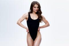 Slank kvinnlig modell i en svart bodysuit på den vita bakgrunden fotografering för bildbyråer