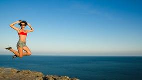 Slank meisje die op de achtergrond van hemel springen royalty-vrije stock afbeelding