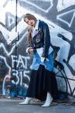 Slank in model die lang flodderig denim en zwarte rok dragen stock afbeeldingen
