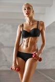 Slank, sexy, blonde, jonge sportvrouw met atletisch lichaam, stelt w stock afbeeldingen