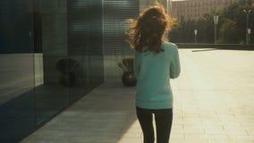 Slank ung brunettte som går i gatan lager videofilmer