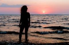 Slank vrouwencijfer in zwempak die en zich verbazende zonsopgang bevinden bekijken royalty-vrije stock fotografie