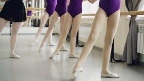 Slanka flicka`-ben i strumpbyxor gör battementtendu under balettkurs med den erfarna lärarinnan som visar stock video