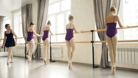 Slanka flickor i body och baletthäftklammermatare gör plie och går på den hållande balettbarren för tåspetsarna under arkivfilmer