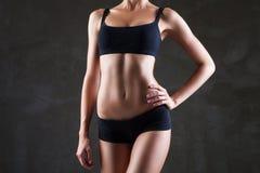 Slanka kvinnas kropp över mörk grå bakgrund Arkivfoto