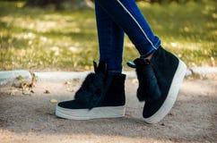 Slanke die benen in jeans in tendenslaarzen met bont en oren op een witte dikke zool worden geschoeid Stock Fotografie