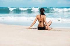 Slanke en gelooide meisje van de close-up het mooie luxe in een zwarte bikini op het strand de oceaan Sexy gelooid lichaam, vlakk Royalty-vrije Stock Afbeeldingen