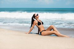 Slanke en gelooide meisje van de close-up het mooie luxe in een zwarte bikini op het strand de oceaan Sexy gelooid lichaam, vlakk Stock Foto